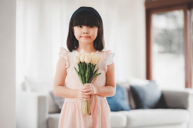 Felice bambina asiatica sorridente che tiene in mano un mazzo di fiori in soggiorno