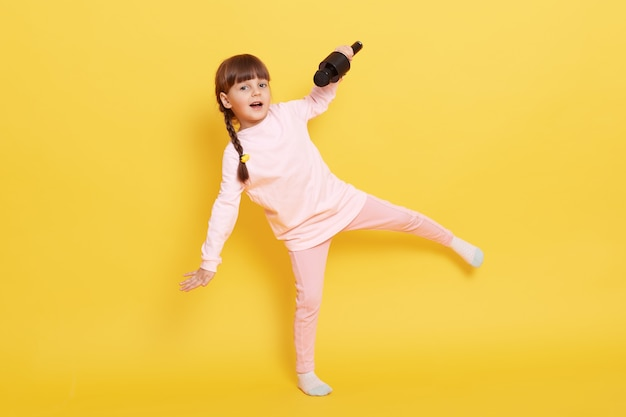 Bambina sorridente felice che salta e canta nel microfono, piccolo cantante che indossa abbigliamento casual in posa isolato su sfondo giallo, bambino con le trecce eseguendo.