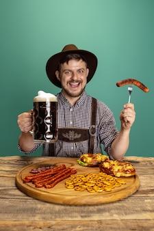 Sorridenti uomo vestito con il tradizionale costume austriaco o bavarese seduto a tavola con cibo festivo e birra isolate su sfondo rosso