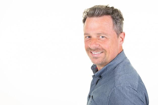 Uomo sorridente felice bello nella condizione casuale blu della camicia isolata sopra lo spazio bianco della copia della parte anteriore del fondo