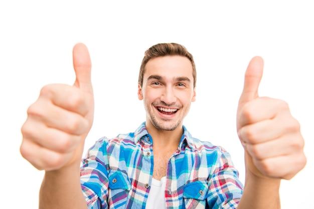 Uomo sorridente felice che mostra i pollici aumenta il segno