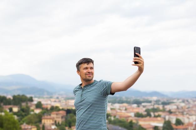 Uomo sorridente felice che prende le foto e selfie con lo smart phone mobile in una città. concetto di viaggio. viaggiatore. vacanze estive.