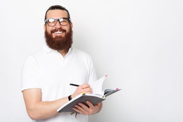 Uomo sorridente felice con la barba che prende appunti nella sua agenda o pianificatore