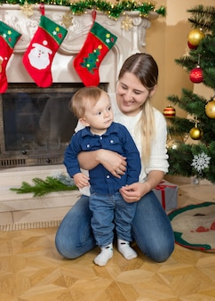 Madre sorridente felice che coccola il suo bambino all'albero di natale