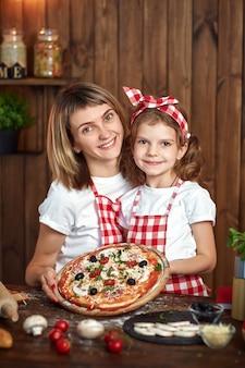 Madre e figlia sorridenti felici con pizza cotta