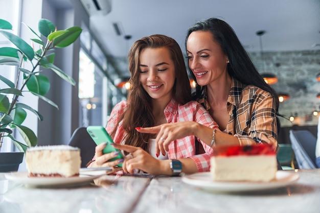 Madre sorridente felice e figlia gioiosa guardando i contenuti video sullo smartphone e divertirsi insieme in un caffè