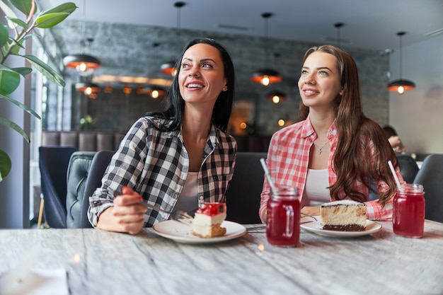 Madre sorridente felice e figlia adolescente gioiosa che mangiano torte e si divertono insieme in un caffè