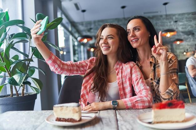 Madre sorridente felice e figlia adolescente gioiosa che scattano foto selfie su una fotocamera del telefono e si divertono insieme in un caffè