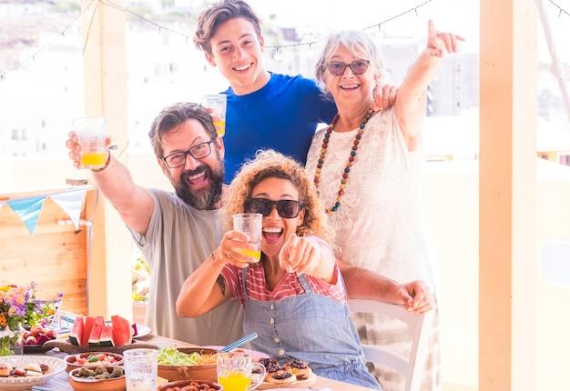 Felice e sorridente gruppo familiare multigenerazionale adulto figlio adolescente e nonna che si godono la festa