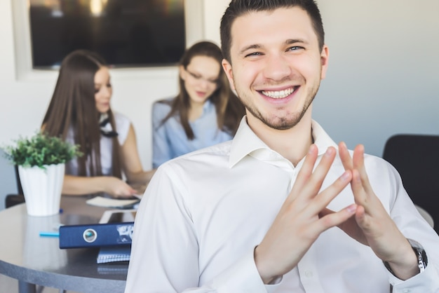 Felice sorridente impiegato maschio, uomo in tuta seduta, conferenza. insegnante bello