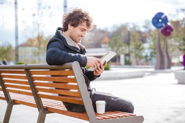 Sorridenti contenti contenti giovane maschio riccio seduto su una panchina nel parco usando tablet e bevendo caffè