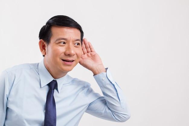 Uomo d'affari positivo sorridente felice che ascolta le buone notizie