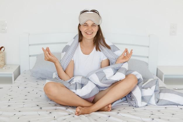Felice donna positiva sorridente con maschera per dormire ed essere avvolta in una coperta seduta con le gambe incrociate sul letto, guardando la telecamera con un sorriso affascinante, mantenendo il gesto dello yoga del peccato della mano.