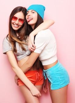 Amici graziosi sorridenti felici che abbracciano sul rosa