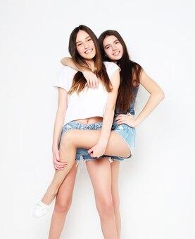 Amici graziosi sorridenti felici che abbracciano su bianco