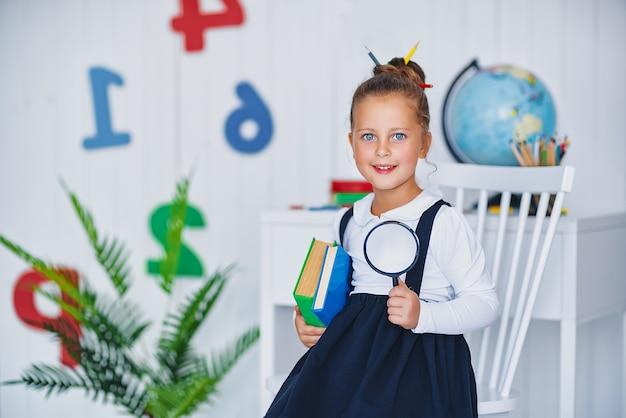 Allievo sorridente felice alla scrivania. bambino in classe con matite, libri. ragazza del bambino della scuola primaria.