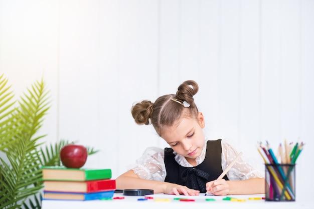 Allievo sorridente felice alla scrivania. ragazza in classe con matite, libri. ragazza del bambino della scuola primaria.