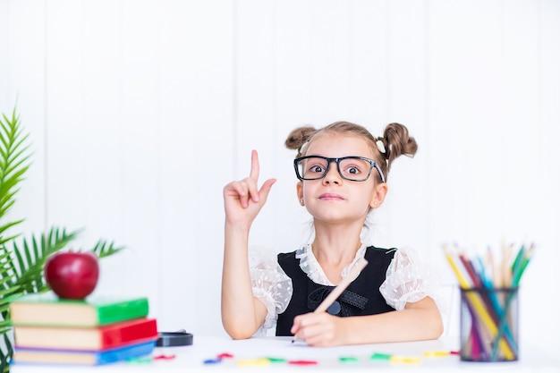 Allievo sorridente felice alla scrivania che punta il dito. ragazza in classe con matite, libri. ragazza del bambino della scuola primaria.