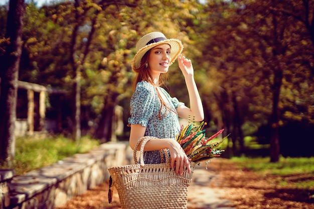 Una ragazza rossa sorridente felice con un cappello di paglia vestito svolazzante cammina nell'estate indiana del parco autunnale