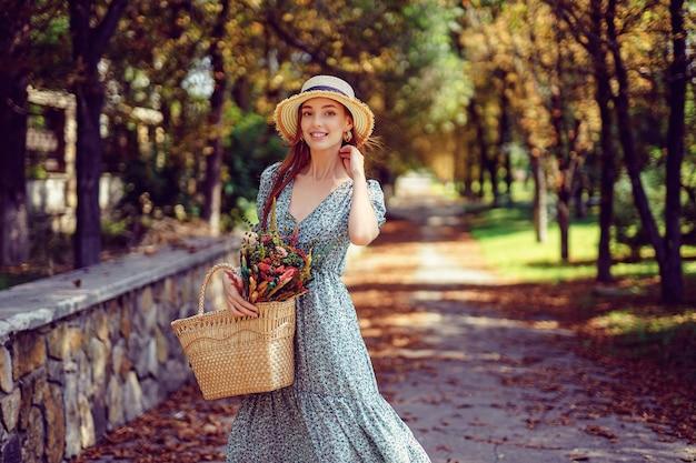 Una ragazza rossa sorridente felice in abito svolazzante cammina nel concetto di estate indiana del parco autunnale
