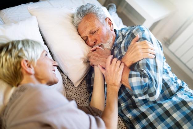 Felice coppia senior sorridente innamorata che abbraccia e lega con vere emozioni a casa