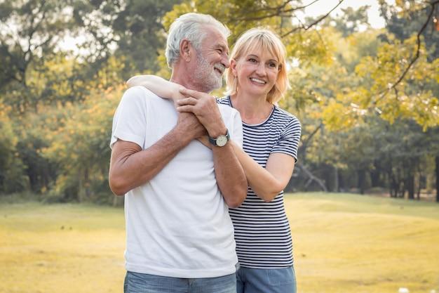 Sorridere felice delle coppie senior in un parco in vacanza.