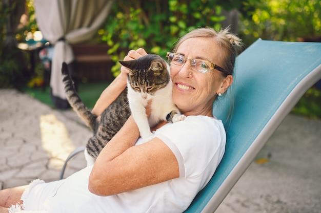 Donna anziana senior sorridente felice in bicchieri rilassante nel giardino estivo all'aperto, abbracciando gatto soriano domestico