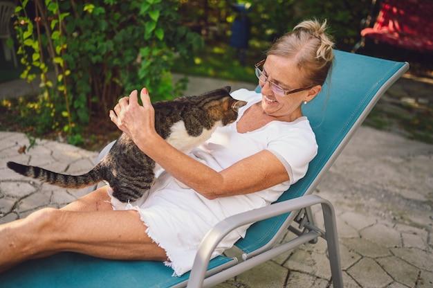 Donna senior sorridente felice in bicchieri rilassante nel giardino estivo all'aperto, abbracciando gatto soriano domestico