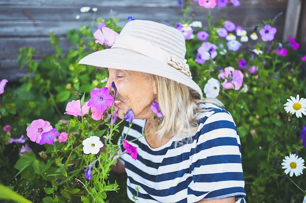 Donna senior sorridente felice che posa nel giardino estivo con fiori in cappello di paglia.