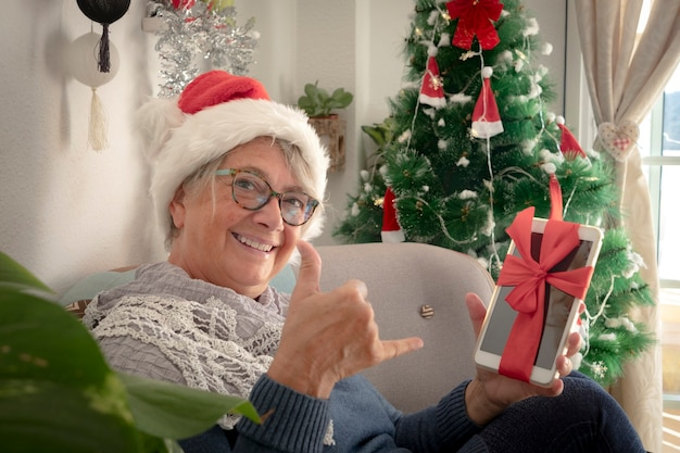 Felice e sorridente donna anziana che indossa un cappello di babbo natale con in mano una tavoletta digitale come regalo di natale - buon natale a casa per un anziano pensionato che si gode le vacanze