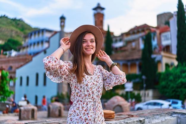Ragazza sorridente felice del viaggiatore contro lo sfondo dei bagni dello zolfo nel distretto di abanotubani di vecchia città di tbilisi, georgia