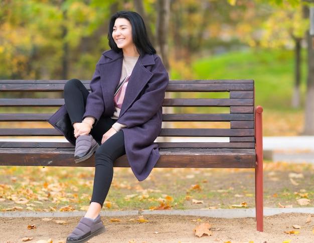 Giovane donna alla moda sorridente felice che si siede su una panca di legno rustica in un parco in autunno con foglie colorate sugli alberi