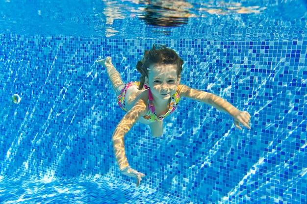 Felice sorridente bambino subacqueo in piscina, bella ragazza nuota e divertirsi. sport per bambini in vacanza estiva in famiglia. vacanza attiva