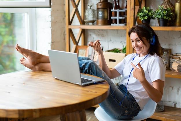 Donna sorridente felice in cuffie blu davanti al monitor di un laptop a casa mette i piedi sul...