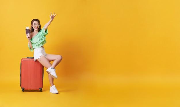 La donna sorridente felice si è vestita in vestiti dell'estate con bagagli che godono della loro vacanza di vacanze estive nel giallo con lo spazio della copia.