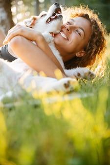 Una donna sorridente felice in un abbraccio con un animale domestico giace su un prato verde in un parco cittadino in estate