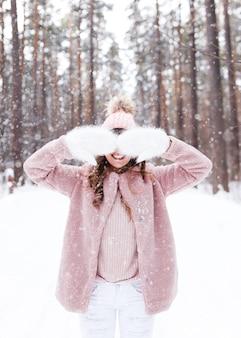 Donna sorridente felice in un cappotto di pelliccia cammina e ride nella foresta invernale