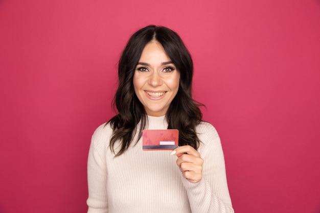 Donna sorridente felice che tiene la carta di credito isolata sullo sfondo rosa.