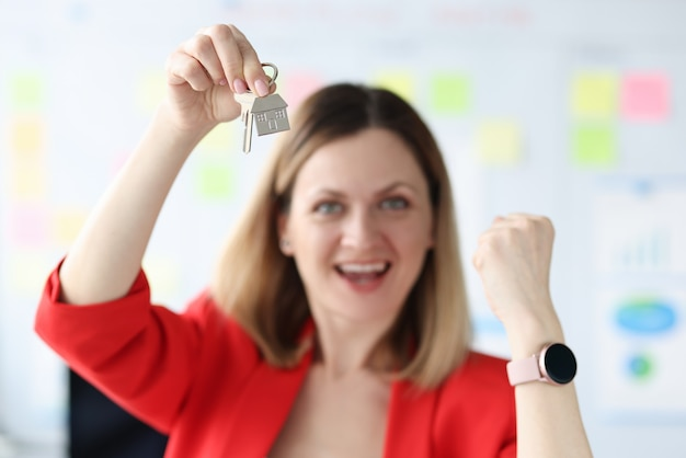 Donna sorridente felice che tiene le chiavi dell'appartamento