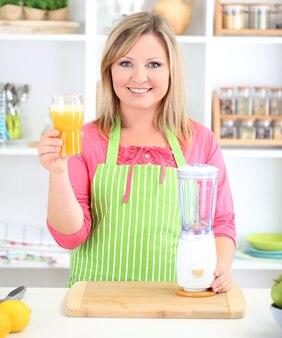 Donna sorridente felice in cucina che prepara cocktail di frutta fresca