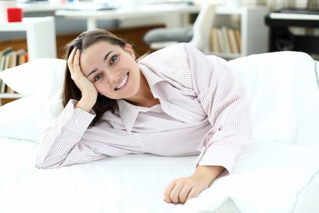 La donna sorridente felice si trova sul primo piano del letto