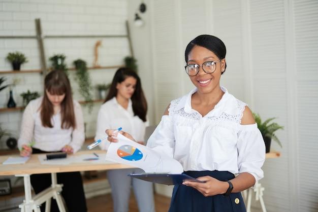 La donna sorridente felice esamina i grafici e le carte di lavoro in ufficio sullo sfondo della squadra femminile.