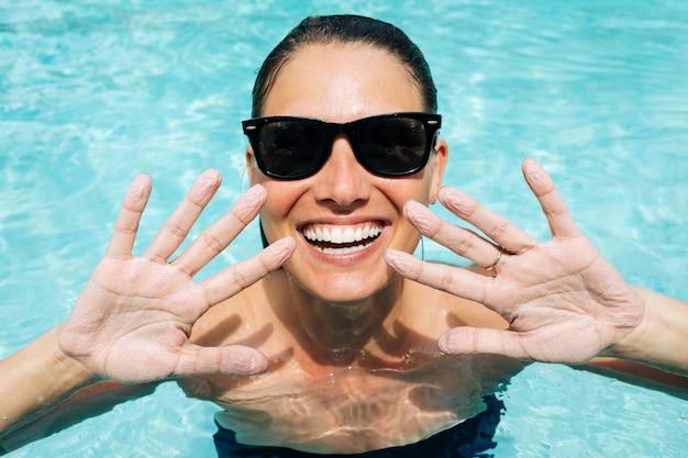 La donna sorridente felice che mostra le dita ha ottenuto rugosa