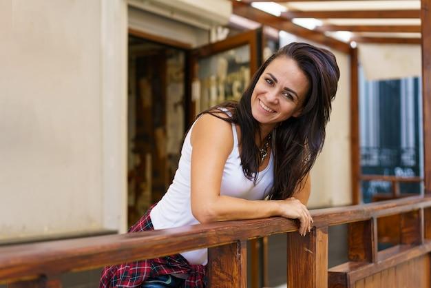 Felice donna sorridente in piedi sulla veranda caucasica ragazza bruna in abiti casual veranda in legno terrazzo