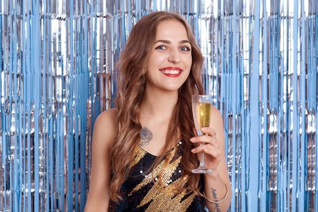 Felice donna sorridente con champagne guardando direttamente la fotocamera, tenendo il bicchiere in mano, ha labbra rosso brillante