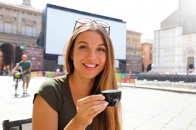 Donna sorridente felice con la tazza di caffè sul paesaggio italiano soleggiato