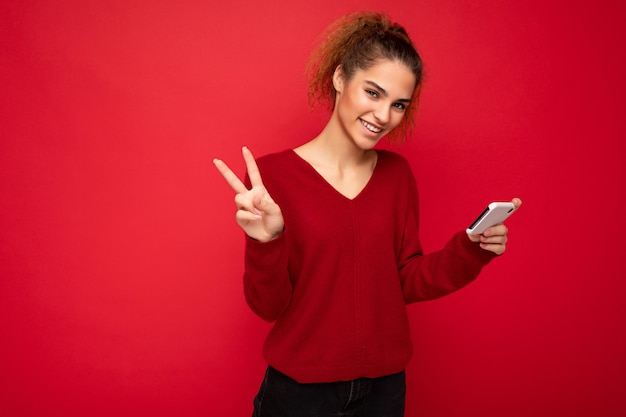 Donna sorridente felice con i capelli ricci raccolti che indossa un maglione rosso scuro
