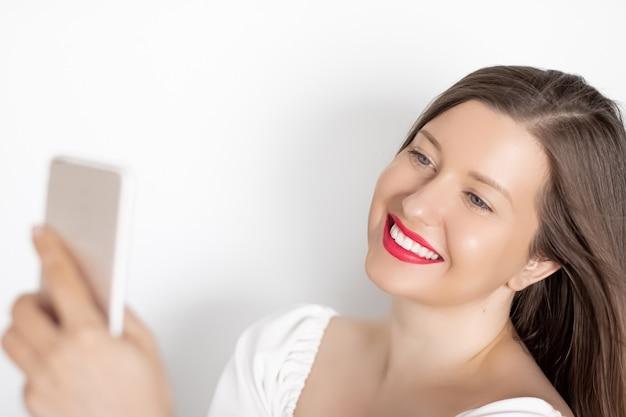 Donna sorridente felice con lo smartphone che fa una videochiamata o che scatta selfie su sfondo bianco tecnologia e concetto di comunicazione delle persone