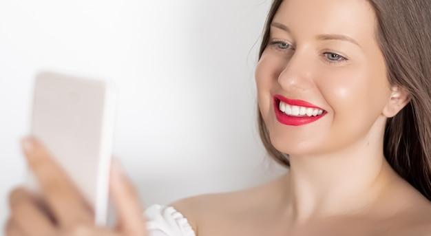 Donna sorridente felice con lo smartphone che ha una videochiamata o che scatta un ritratto di selfie su sfondo bianco persone tecnologia e concetto di comunicazione