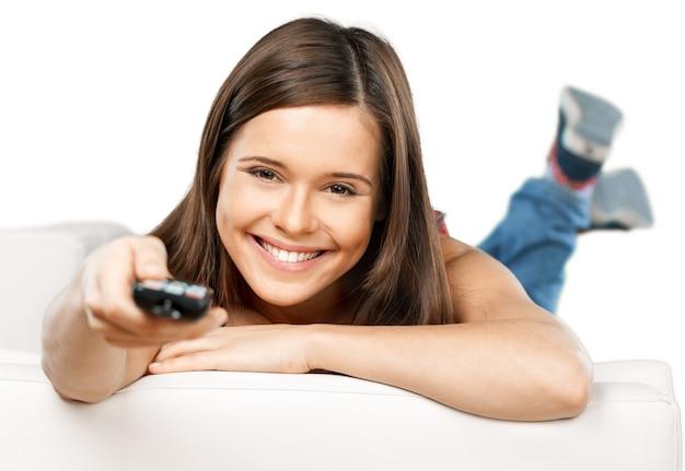 Donna sorridente felice con telecomando della tv